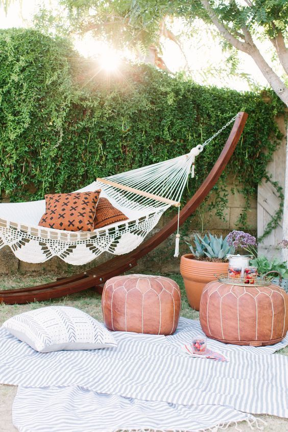 a boho backyard space with a living wall, a hammock ona stand, leather poufs, potted plants and blooms and striped rugs