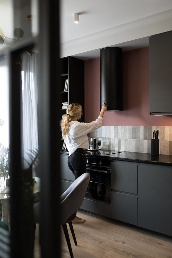 a minimalist graphite grey kitchen with a creative skinny tile backsplash and a mauve accent wall plus a black round hood