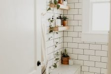 08 a neutral bathroom with white subway tiles, penny tiles on the floor and potted plants plus neutral textiles