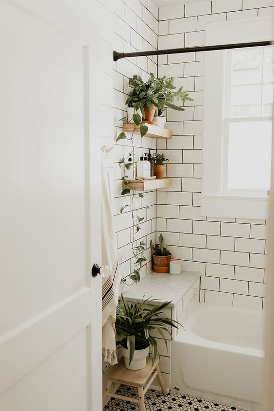 a neutral bathroom with white subway tiles, penny tiles on the floor and potted plants plus neutral textiles