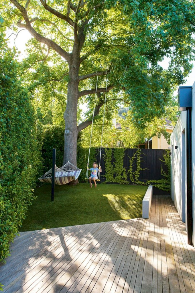 a small and dreamy backyard with living walls, a large tree, grass, a hammock and a swing, with a wooden deck
