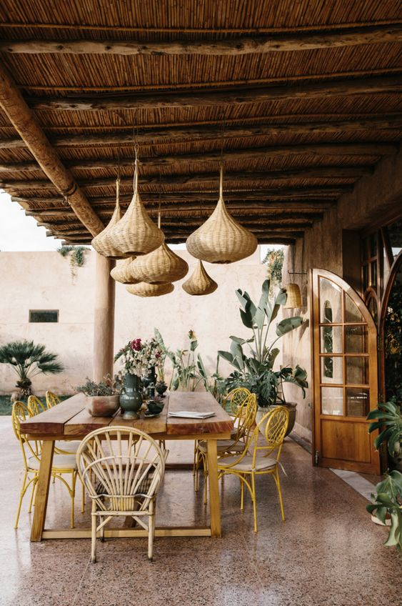 a tropical outdoor dining zone with a wooden table, woven pendant lamps, rattan chairs and potted greenery