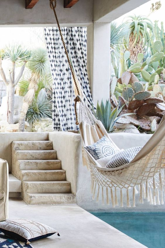 a boho desert outdoor space with a concrete terrace and a pool, a hammock with fringe and pillows, lots of cacti around