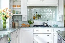 09 a chic white kitchen with an aqua tile backsplash and a hidden kitchen hood covered like a cabinet, grey stone countertops