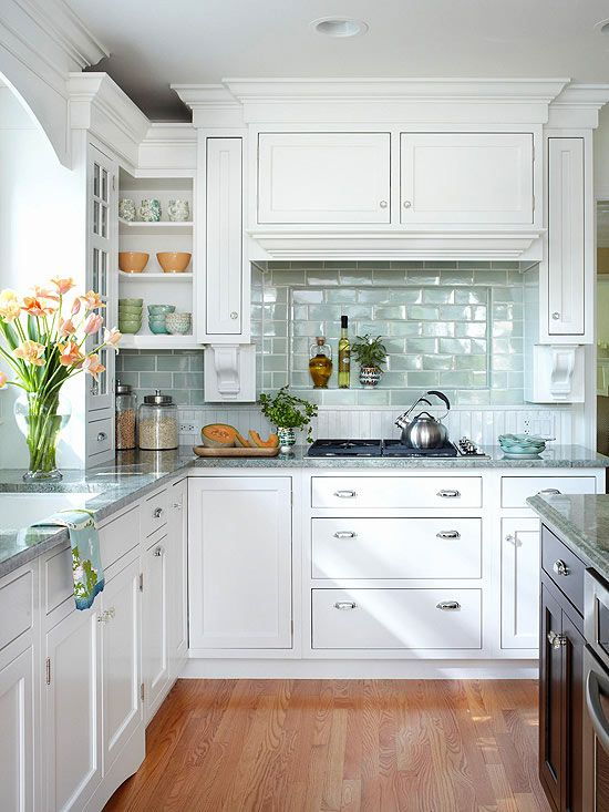 a chic white kitchen with an aqua tile backsplash and a hidden kitchen hood covered like a cabinet, grey stone countertops