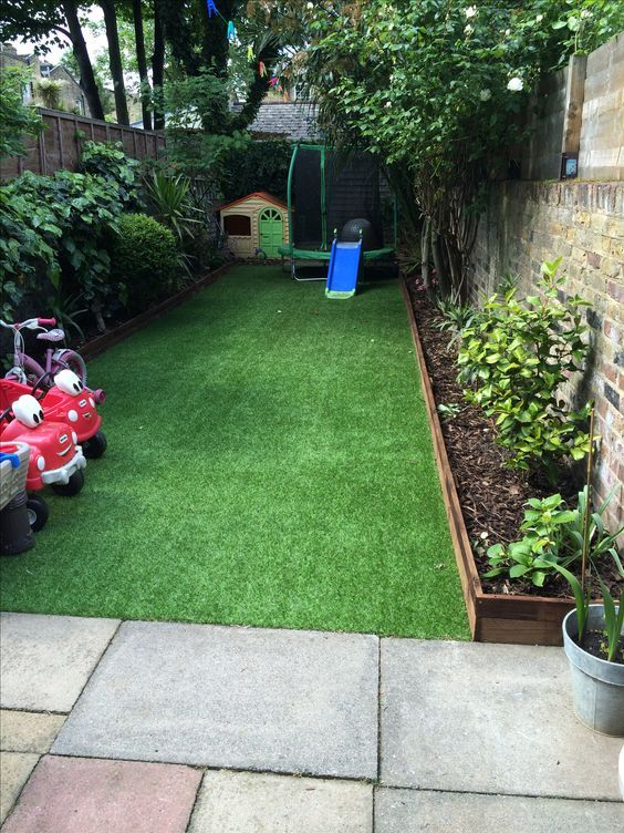 a small backyard turned into a kids' entertainment zone with a kid house, some cars and other stuff and covered with artificial turf