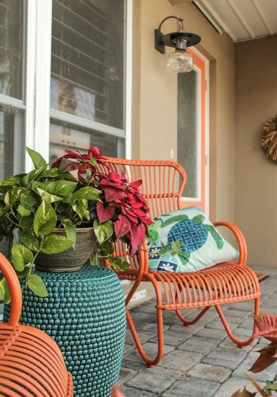 a small porch sitting space with orange rattan chairs, a blue side table with a potted plant and some cool printed pillows