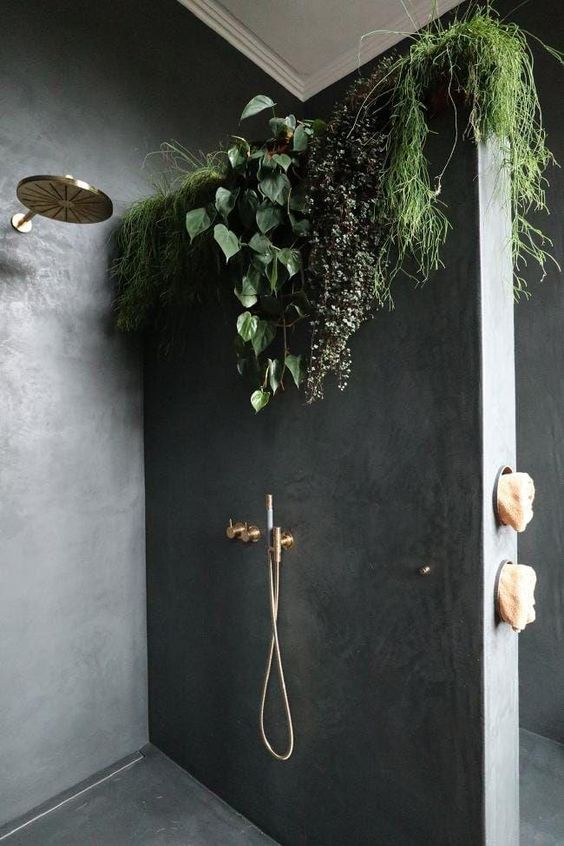 a minimalist bathroom done with concrete and with climbing plants on the wall to feel like having a shower outside