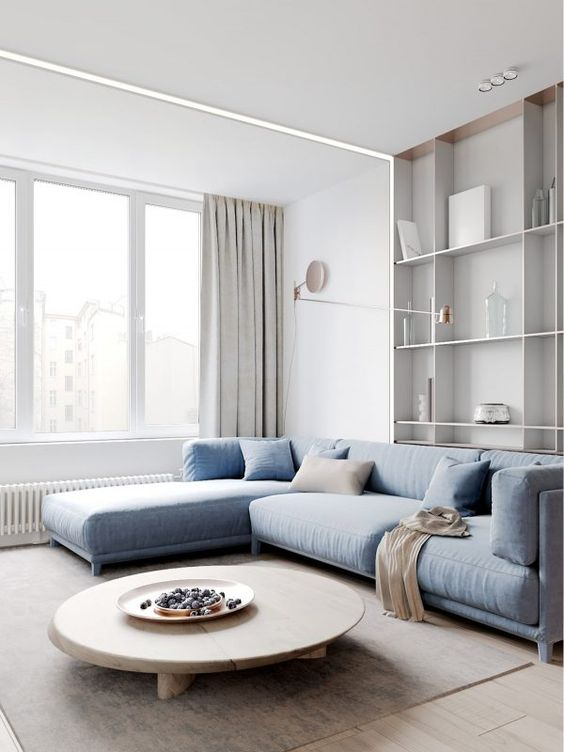 a beautiful minimalist living room with a blue sectional, grey curtains, a low round table and cool built-in shelves