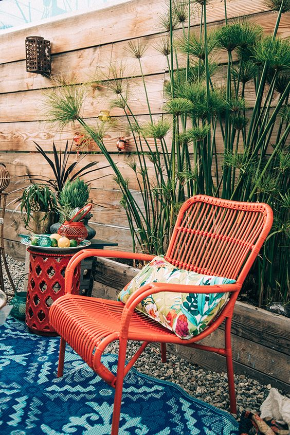 a red rattan chair with a colorful pillow and a bold rug, some potted plants for a colorful outdoor space