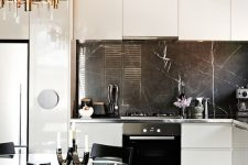 11 a refined contemporary kitchen with sleek white cabinets, a black marble backsplash and a built-in hood plus a glam chandelier and a cool dining set