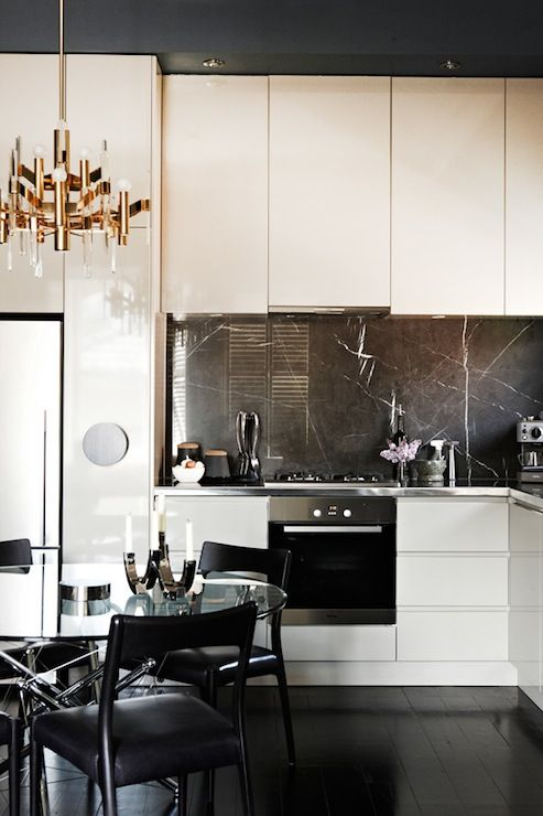 a refined contemporary kitchen with sleek white cabinets, a black marble backsplash and a built in hood plus a glam chandelier and a cool dining set
