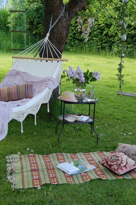 a refined outdoor space with a hammock attached to the trees, printed pillows and rugs, a metal side table and blooms