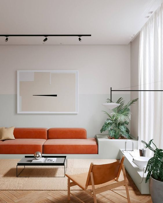a beautiful minimalist living room with a pale grey color block wall, an orange sofa, a jute rug and a leather chair