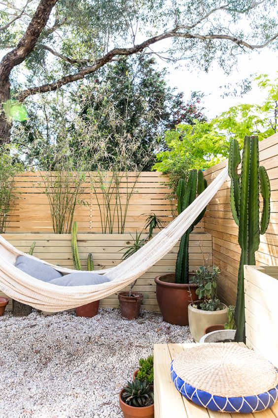 a boho outdoor nook with a hammock and pillows, potted plants and cacti plus a jute pouf is a lovely space inspired by deserts