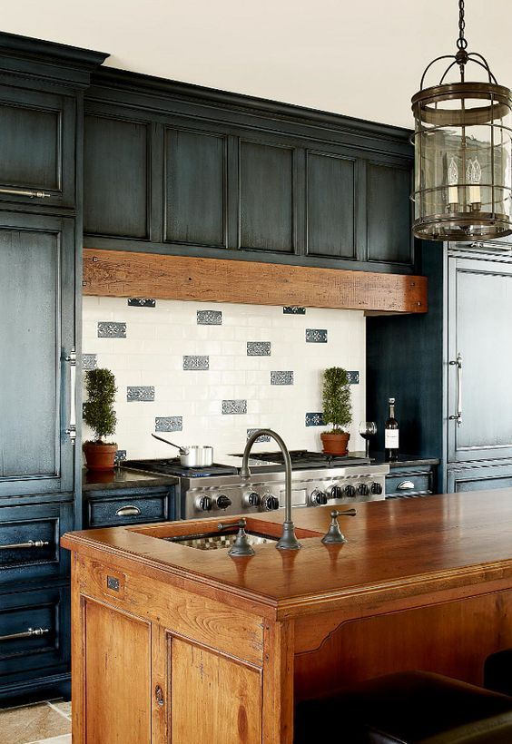 a refined vintage kitchen with whitewashed blue cabients, a tiled backsplash and a hidden hood, a wooden kitchen island and a pendant lamp