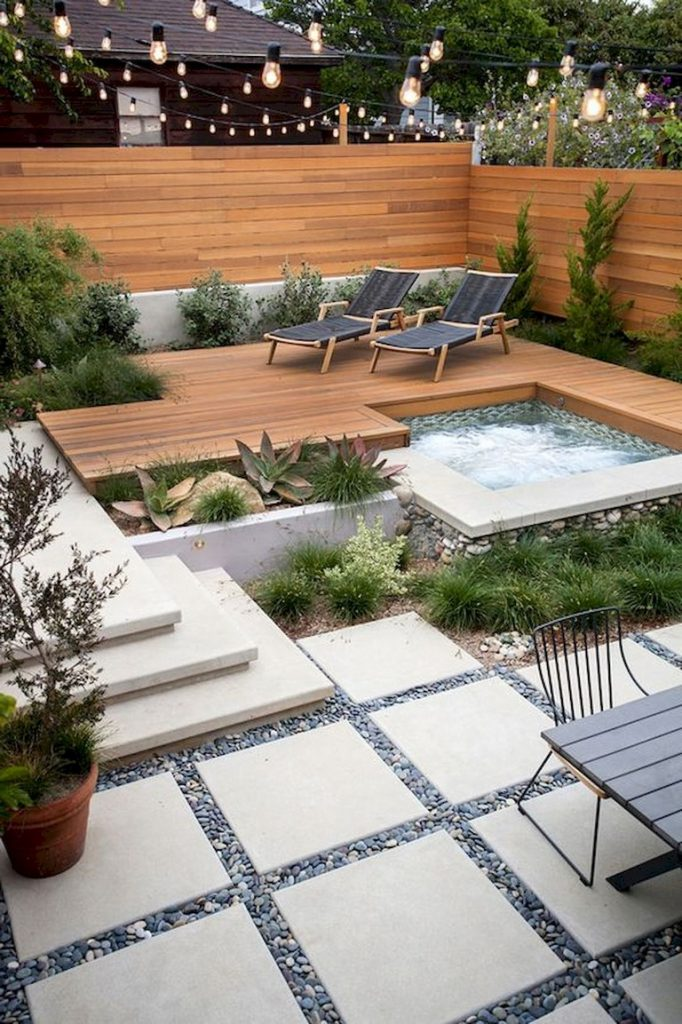 a small modern backyard with a stained fence and deck, with a hot tub, growing plants and loungers, with a dinign table and chairs