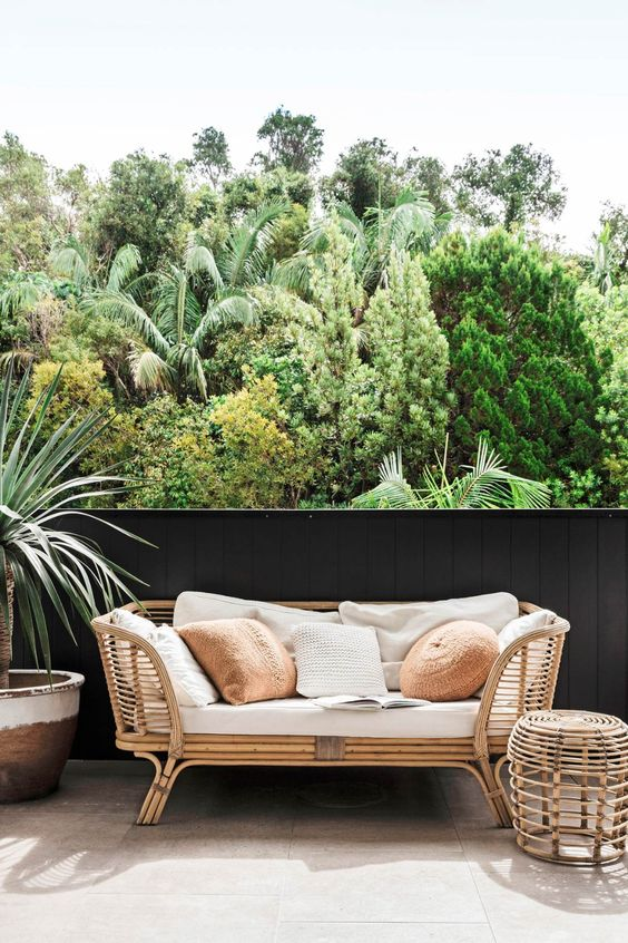 a balcony with a rattan daybed, a side table and a potted plant plus lots of pillows to style the sofa