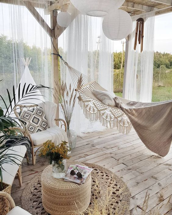 a breezy outdoor boho deck with a pergola, some rattan furniture, a jute pouf and jute rugs, a hammock and paper lamps