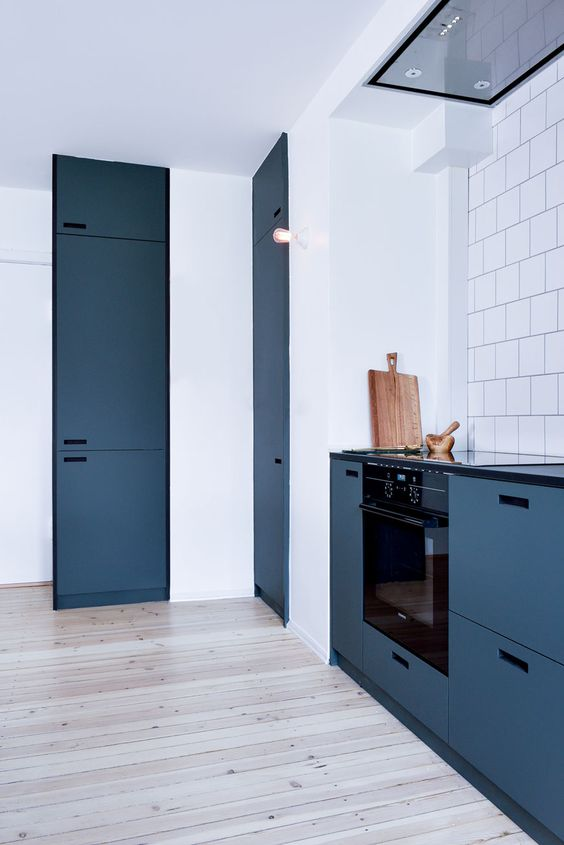 a chic minimalist Royal blue kitchen with black built-in appliances and black touches looks amazing