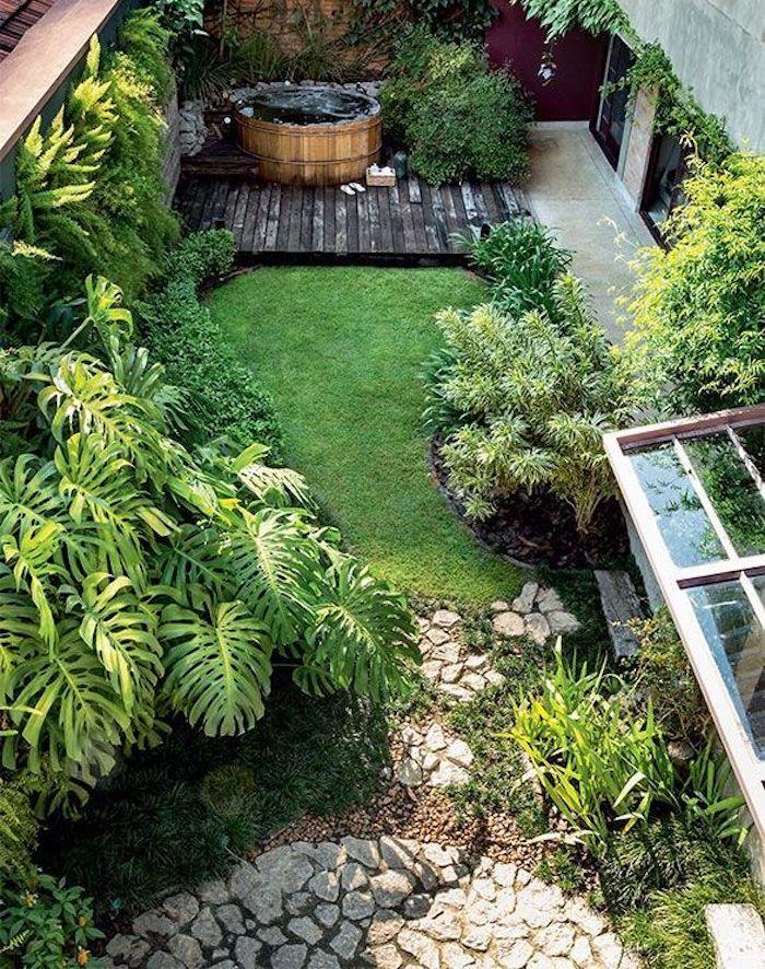 a gorgeous small backyard with grass and lots of plants, with a desk with a wooden hot tub and a stone clad space