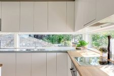 13 a sleek minimliast white kitchen with a window backsplash and an integrated hood hidden inside a cabinet is amazing