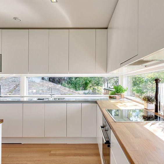a sleek minimliast white kitchen with a window backsplash and an integrated hood hidden inside a cabinet is amazing