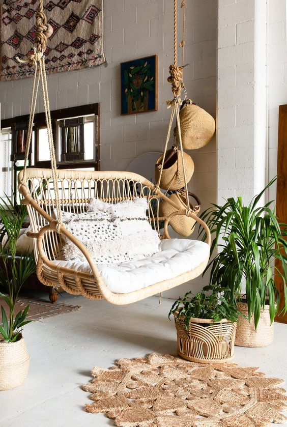 a boho porch with a double rattan chair with neutral cushions and pillows, a jute rug, some baskets hanging and potted plants