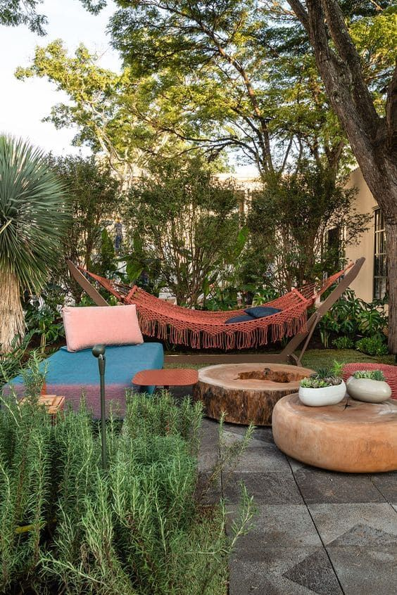 a bright outdoor space with a daybed, a wood slice table, a red hammock on a stand and potted greenery and growing