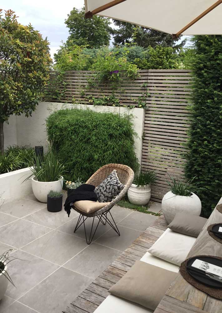a contemporary backyard with a planked screen, with a tiled floor, potted grasses and greenery, a small dining set with pillows and a woven chair