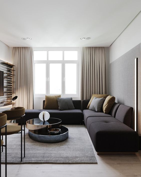a gorgeous minimalist living room with a big black sectional, grey and mustard pillows for a touche of color and mustard chairs