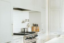 14 a stylish farmhouse kitchen in creamy shades, with shaker cabinets and a hidden hood plus a dining space here