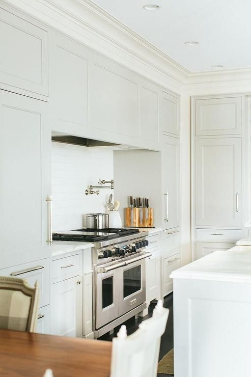 a stylish farmhouse kitchen in creamy shades, with shaker cabinets and a hidden hood plus a dining space here