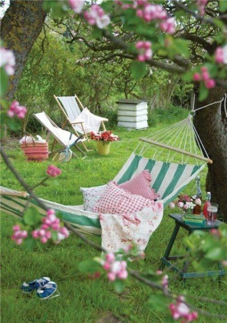 a bright summer garden with a striped hammock attached to the trees and printed pillows, some folding chairs and books around