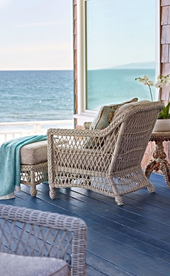 a coastal porch with a rattan chair and an ottoman, with blue textiles and a gorgeous view of the sea is amazing