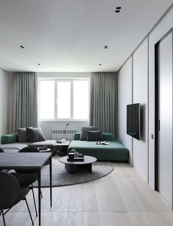 a lovely minimalist living room with a green and grey sofa, grey and green pillows, green curtains and chic furniture