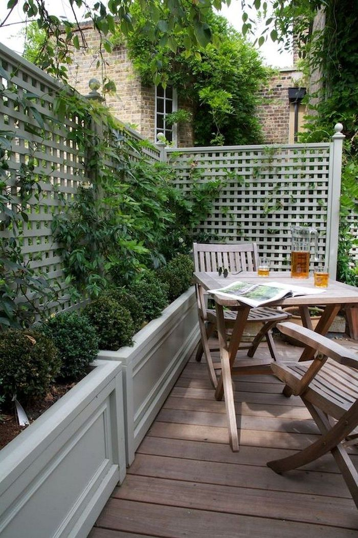 a small and cozy backyard with a deck, a simple wooden outdoor furniture set, potted greenery and climbing plants is very cozy