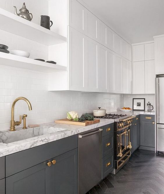 a stylish grey and white kitchen with a white subway tile backsplash, a white stone countertop and a hood hidden in a cabinet is super chic