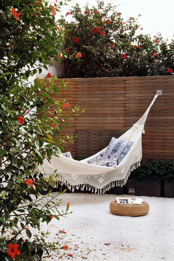 a chic outdoor space with greenery and blooms, a white hammock with printed pillows, a small jute pouf and a glass of wine