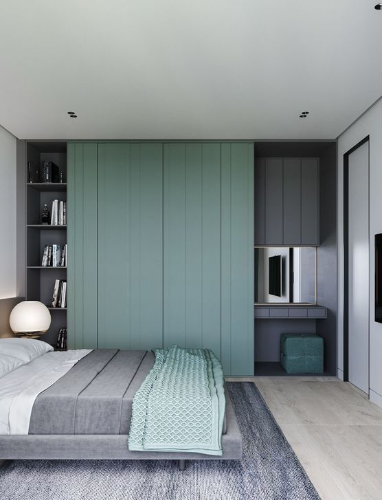 a minimalist bedroom done in graphite grey and greens, with built-in shelves, and a vanity space with a green pouf