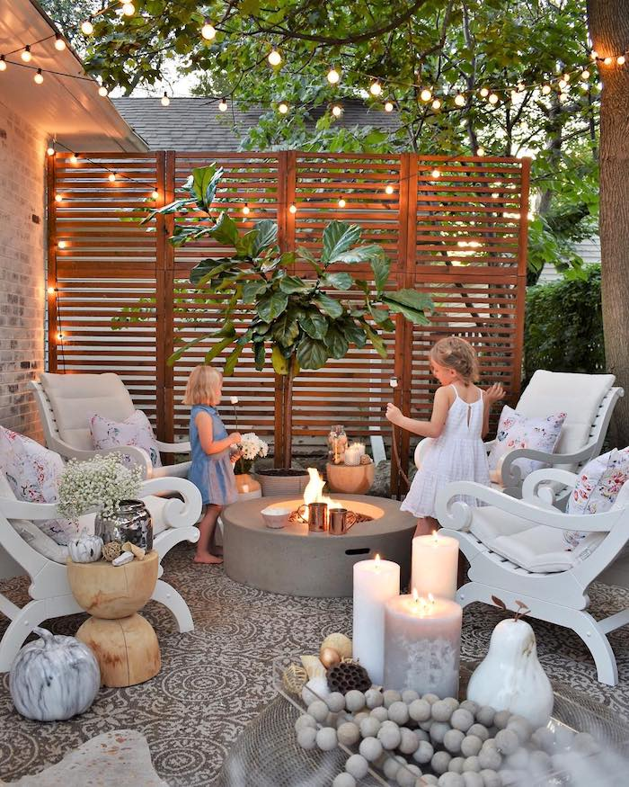 a small and inviting backyard with a screen and string lights, with a fire pit and elegant white chairs with pillows, lots of candles and wooden tables