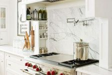 16 a stylish white kitchen with shaker style cabinets, a white marble backsplash, a chic kitchen hood done like a cabinet