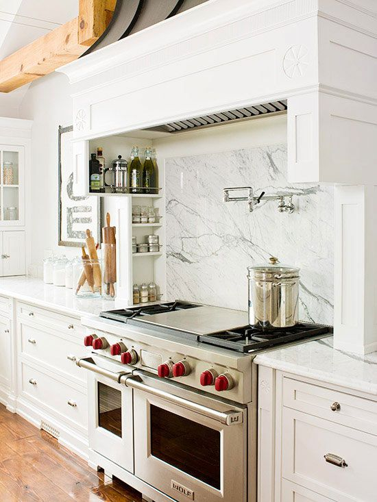 a stylish white kitchen with shaker style cabinets, a white marble backsplash, a chic kitchen hood done like a cabinet