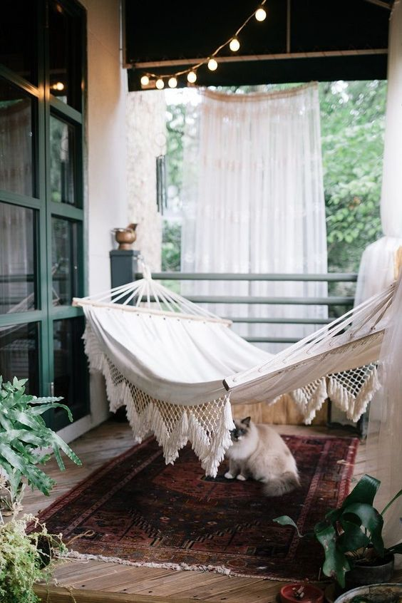 a boho porch with curtains, string lights, a hammock, a boho rug and potted plants is a very cool idea for relaxing outdoors