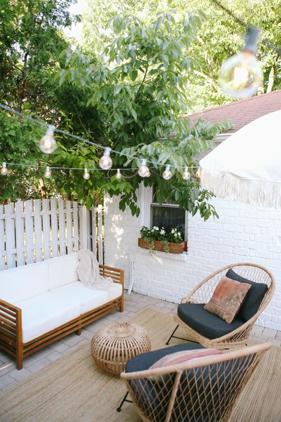 a cool outdoor nook with rattan furniture, a rattan pouf, string lights and lots of greeneyr around is a lovely space