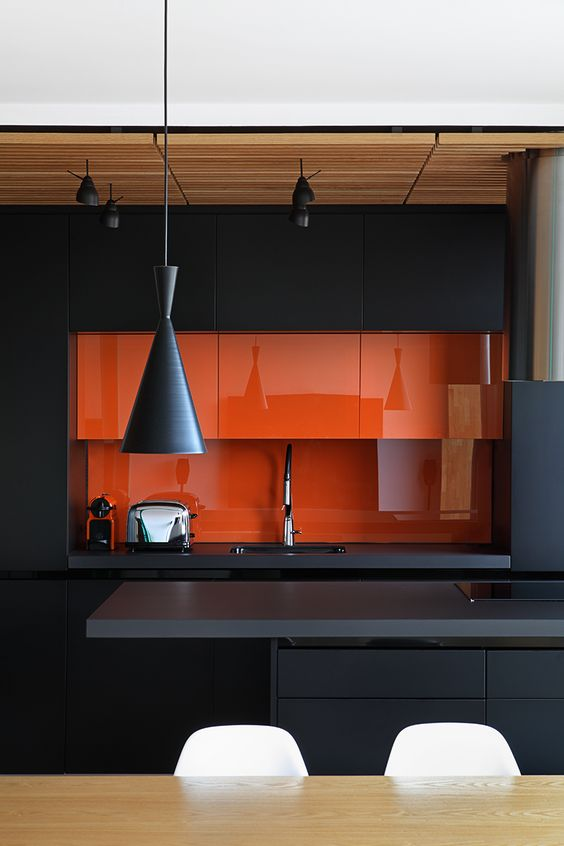 a minimalist black kitchen with a sleek orange backsplash and mini cabinets that are a gorgeous color statement in the space