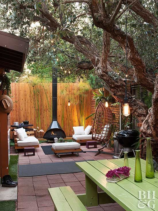 a small and lovely backyard with a fireplace zone with elegant outdoor furniture, a grill and a small dining space with green outdoor furniture