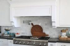 17 a white rustic kitchen with shaker cabinetry, a grey kitchen island and a hidden hood covered like a cabinet