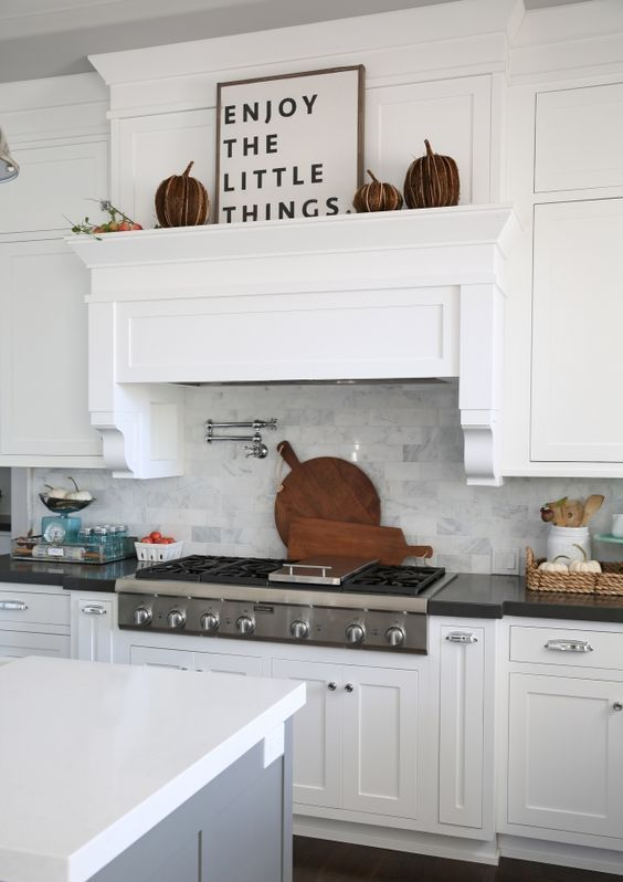 a white rustic kitchen with shaker cabinetry, a grey kitchen island and a hidden hood covered like a cabinet