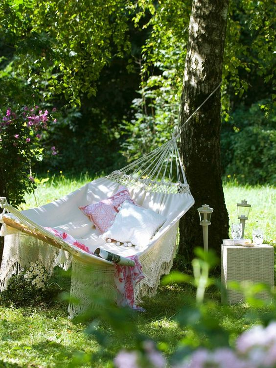 a chic summer garden with a hammock attached to the trees, a wicker side table and some garden lamps plus printed pillows